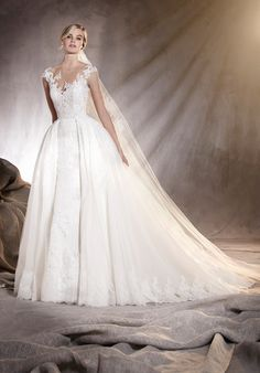 A wedding dress with an overskirt for brides who cannot decide between a mermaid cut or a princess cut. The sleeveless sweetheart neckline and the fabrics -tulle and lace- and thread embroideries and gemstone decorations let this dress shine with a light of its own, making for a dazzling bride. The Knot provides price estimates to give you a general idea of the cost of a dress. Please visit retailers in your area for exact pricing. Prices will vary by region.