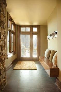 A hinged in-swing patio door with sidelight and transom windows maximizes the natural light of this entryway. | Andersen Windows + Doors
