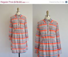 Vintage 1960s colorful cotton stripe dress. Gold buttons down the front for closure. Flattering nipped waist fit. A line skirt. Lined inside.