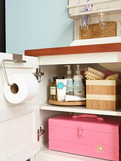 Stow bulky items -- towels, super-size bottles, baskets of bath oils -- under the sink. Here, a paper towel holder keeps extra rolls of toilet paper out of sight. And a lazy Susan is the perfect way to ensure access to that back bottle of hair spray.