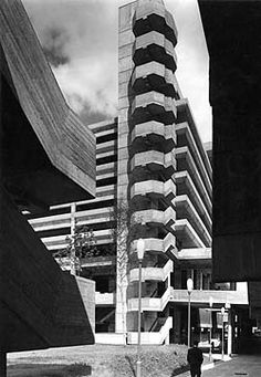 a black and white photo of a corner of a multi storey car park made out of concrete