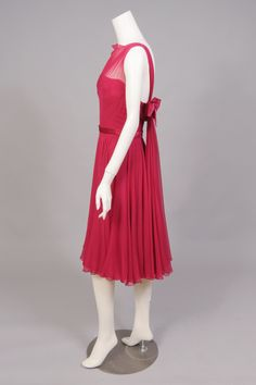 Frank Starr cocktail dress (side view) | United States, 1950's | Raspberry red silk chiffon is accented with matching satin | There is a sheer bodice, a strapless top, and a very full skirt. The back of the dress has a lovely drape over the right strap, with a satin bow on the left side above floating chiffon panels