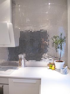 Modern kitchen, mirror tiled wall with a cool white perimetric wall hood.
