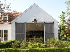 Charming Belgian country home with painted white brick and chunky sliding shutters!  Use as many lanterns as possible!
