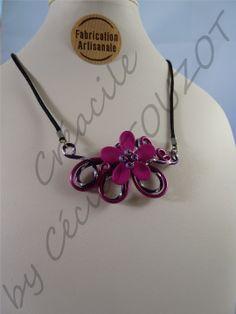 Collier avec fleur et perles - ORCHIDEE FUCHSIA  Collier en fils aluminium rose fuchsia et violet prune monté sur un tour de cou en galon brillant noir. Longueur réglable. Composé d'une fleur type orchidée rose fuchsia et de perles violettes. Un collier tout en finesse comme on aime les porter tous les jours. Un basique à avoir absolument dans sa boîte à bijoux.