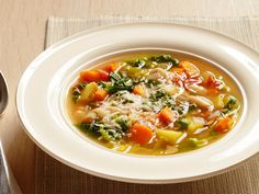 Minestrone With Parmigiano-Reggiano : Swiss chard, carrots, cannellini beans and spinach come together in Bobby Flay's version of this hearty vegetable soup.