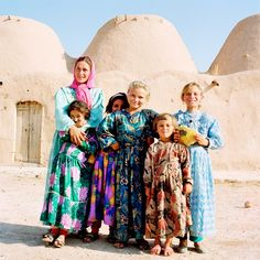 Group of girls in front of dome clay buildings.