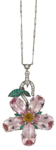 Art Deco platinum and diamond morganite pendant. Unusual modified fancy cut pear shape morganite 'petals', separated by caliber cut emerald 'leaves', center features a beveled modified round cut yellow sapphire; white diamond set 'branch' with delicate articulated emerald 'leaves' serving as bail. Elongated platinum link chain. #FreemansAuction