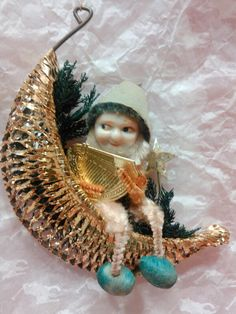 Vintage chenille gnome ornament holding harp sitting in gold crescent basket surrounded by greenery.