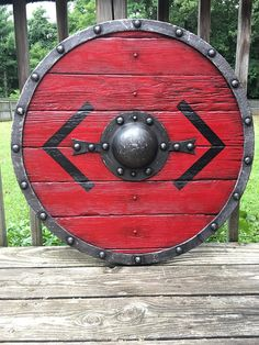 Viking shield of Bjorn son of King Ragnar has a 29 diameter constructed of distressed poplar planks and leather rim painted and highlighted to look like forged iron. The shield boss on this magnificen Escudo Viking, Viking Life, Viking Warrior, Rey Ragnar, Larp, Viking Shield Design, Arte Viking, Viking Party, Medieval Shields