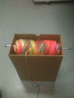 Ingenious way to hold your yarn while crocheting. Box, one large knitting needle, and yarn