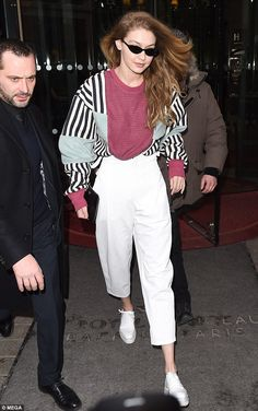 Pitcher-perfect: Gigi Hadid goes back to the 80s in a baseball-inspired sweatshirt as she leaves her Paris hotel