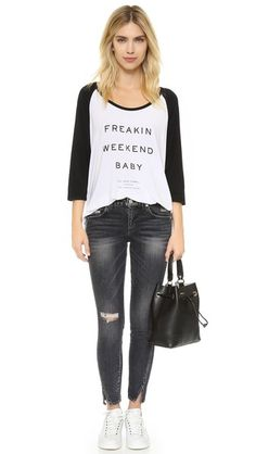 Bold lettering accents this two-tone The Laundry Room tee. Comfortable, boxy silhouette. Side slits. 3/4 raglan sleeves.