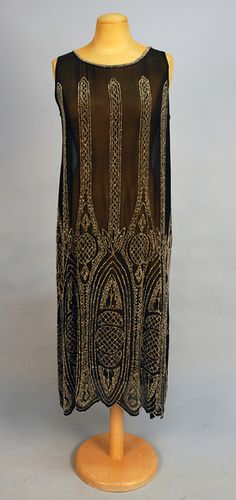 Heavily beaded sleeveless black chiffon, the bodice having vertical bands widening on skirt into ovals and rounds with lattice decoration, scalloped hem. 1920 Flapper Dresses, Beaded Flapper Dress, 1920s Dress, Vintage Dresses, Vintage Outfits, Flapper Style, Art Deco Fashion, Retro Fashion, Vintage Fashion