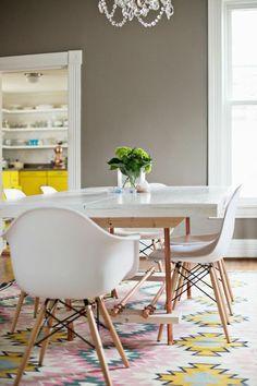 Der Teppich besteht aus hellen Aztekenmustern, passend zu weißen Eames Stühlen