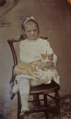Tintype: Young girl with ginger and white cat.