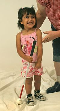 """""""What You Absolutely, Positively Need to Know Before Assessing a Child for O&M Instruction"""" -- a free excerpt from The Art and Science of Teaching Orientation and Mobility to Persons with Visual Impairments by William Henry Jacobson. (Image: young girl with white cane. Adult is leaning down to talk to her.)"""