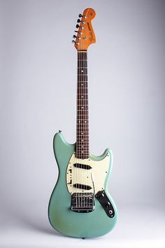 Fender Mustang Model Solid Body Electric Guitar (1965), made in Fullerton, California, serial # L67795, blue lacquer finish, alder body, maple neck with rosewood fingerboard, original grey hard shell case.  This is a very attractive and overall nicely preserved 1965 Mustang, made about a year aft...