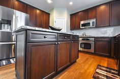 Outdated Cabinets Restrained To A Darker Rich Stain Finish With Black  Shadowing And Pin Striping In Crevices.