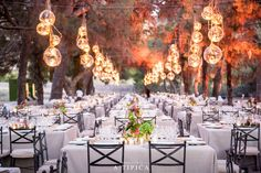 Wedding tables by A-TIPICA in Cartagena, Spain. Floating lights, rectangular tables. Under a pine forest. Pink and green flowers.