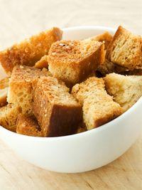 Haal de korstjes van het brood en snijd het overgebleven deel in blokjes. Leg ze ongeveer 15 minuten in de oven tot de stukjes krokant zijn. Je kunt na afloop extra smaak toevoegen met olijfolie. Wil je croutons met nog meer smaak? Doe de stukjes brood dan voor je ze in de oven doet in een plastic zak. Doe er een aantal lepels olijfolie bij en wat kruiden naar smaak. Laat het even intrekken voor je je croutons in spé in de oven bakt.