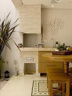 Aproveitamento da varanda com charmosa churrasqueira e móveis clássicos. Revestimento em pedras tipo canjiquinha. Piso em ladrilhos hidráulicos