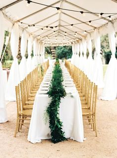 Elegant garden wedding table covered in garland: http://www.stylemepretty.com/texas-weddings/austin/2016/08/20/elegant-winter-garden-wedding/ Photography: Ashley Bosnick - http://www.ashleybosnick.com/