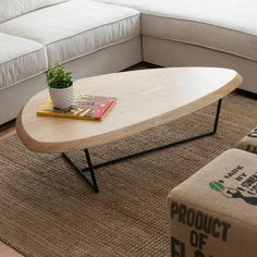 Hull Coffee Table - The Hull Coffee Table features a thick, solid Ash top with a beveled edge and an organic outline that evokes the hull of a ship. The surface is supported by a black, solid steel base. Crafted using FSC®-Certified wood, in support of responsible forest management.