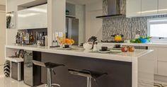 O balcão que separa a cozinha do estar  se estende em toda a área da cozinha e no final dele um bar é incorporado e fica perfeito.O móvel basculante sobre o bar se abre para os dois lados e guarda copos e taças.