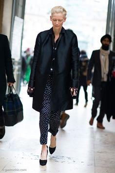 Tilda Swinton luciendo un pantalón de lunares pequeños con una blusa de transparencia negra con lunares grandes. #women #fashion #style #pants #black #hautecouture #couture #mujer #moda #estilo #pantalones #altacostura #negro