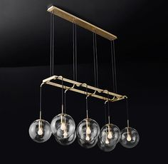 """RH Modern's Languedoc Linear Chandelier 60"""":The character of 1960s French lighting is captured in this chandelier from renowned designer Jonathan Browning. With glass globes suspended from a slender brass frame, the fixture has the appearance of magically floating in space."""