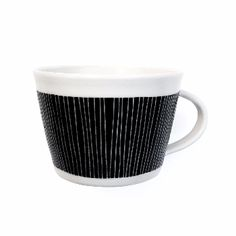 Black Mug: Black mug. Hand thrown and hand-decorated porcelain. All pieces vary due to the hand-made nature of the product. Handmade in Kent, UK by Vicky Hageman.