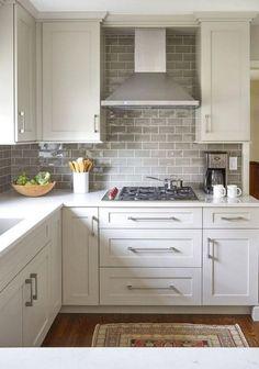 like cabinets, stove hood, tiles, molding seems to ...