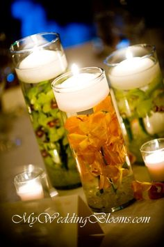 Wedding Centerpiece for the Bride on a Budget: Clear vases with floating candles and flowers. A DIY that's easy, cost effective, and looks magical with a few grouped together!