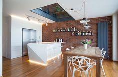 loft avec murs en brique exposés, éclairage indirect et mobilier en bois