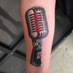 New school microphone tattoo on the inner forearm.