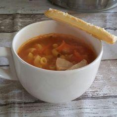Tomatensoep met wortel, kip, pasta en een bladerdeegstaafje er naast.