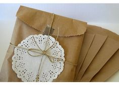 Kraft paper packaging topped off with a doilie and fastened with twine.  I like that you could use a fabric or paper doilie with this.