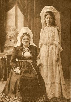 Brietoglaufey: Two women, the one to the left is wearing skautbúningur and the one to the right is wearing a kyrtill.