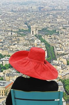 Wearing a red hat with a view of Paris
