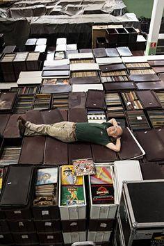 Empresário Zero Freitas, 60, deita sobre caixas com mais de 250 mil discos de vinil Leia mais: