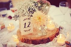 Love the wooden tree trunk slices for the centerpiece bases, rustic table numbers and soft romantic flowers