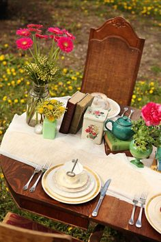 Fresh flowers, tea pots, and books for a vintage garden party theme