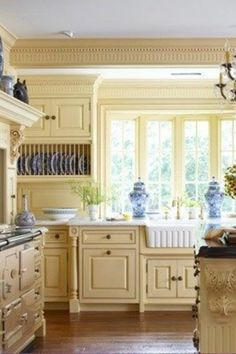 buttercream kitchen cabinets, blue and white willow ware, farmhouse apron sink, aga stove, mantel range surround