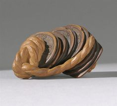 """CARVED WOOD NETSUKE 19th Century In the form of ancient coins strung together on a rope; the third coin spins freely. Length 2"""" (5 cm)."""