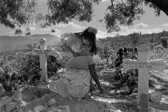 EL SALVADOR. San Salvador. 1991. A daughter comforts her mother who passed out while grieving at the grave of her son who was killed by government death squads.