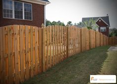 Arched shadowbox wood privacy fence with french gothic posts.