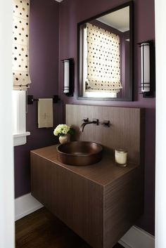 Morgante Wilson Architects installed a floating vanity in this small Powder Room.  Plumbing and sconces are Bronze to keep a casual feel.