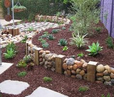 Reclaimed  Retaining wall.This retained wall was built using recycled crimped wire mesh. reclaimed wooden posts and rocks that were dug up from the ground – brilliant idea for shaping your garden.