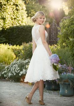 This exquisite embroidered knee-length wedding gown from Essense of Australia is made from gorgeous lace on tulle, and features a pretty lace illusion neckline and back. A Diamante-encrusted band slims the waist, and the back zips up under coordinating fabric-covered buttons.